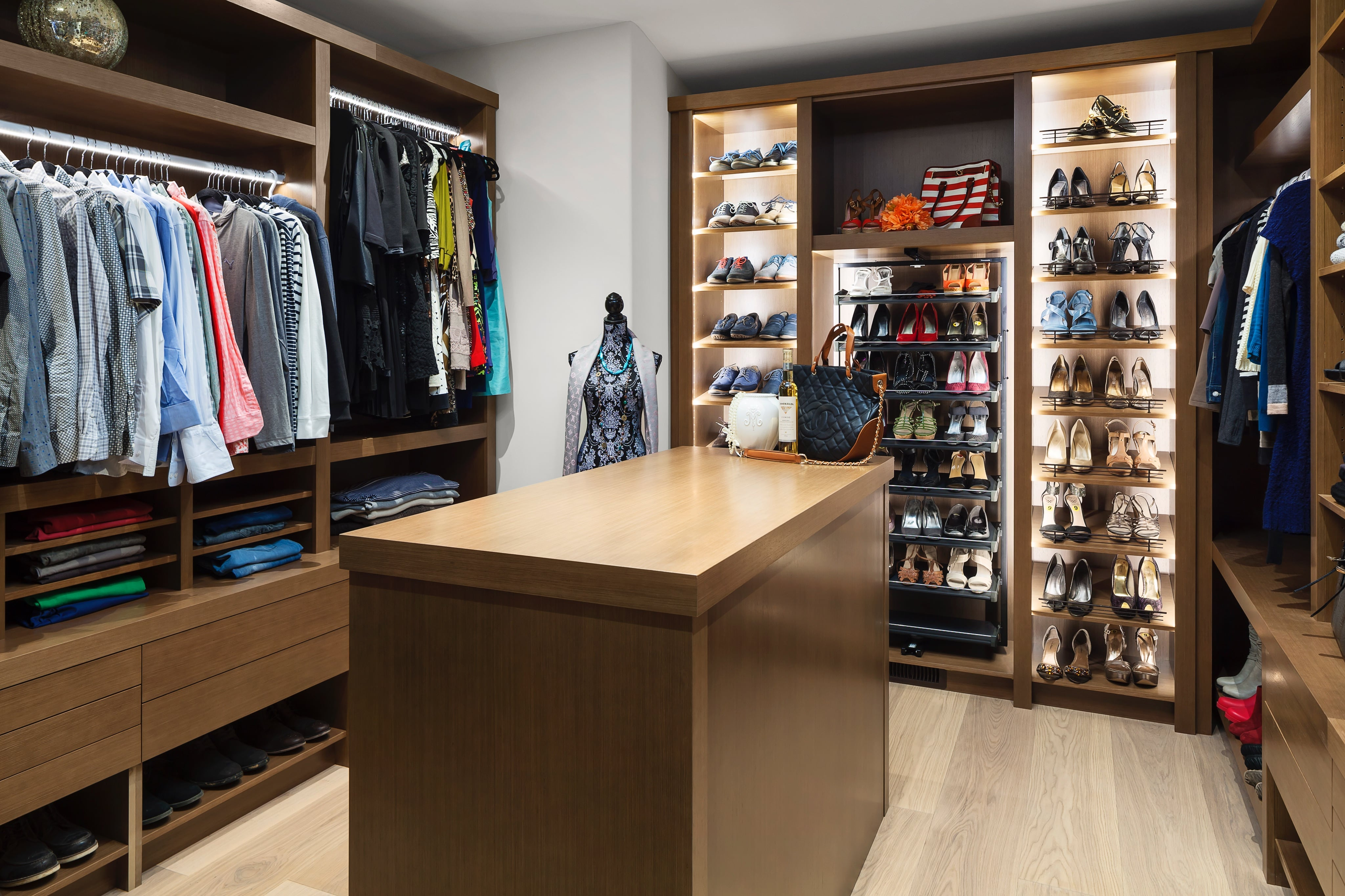 Walk-in closet filled with clothes and lit with custom light